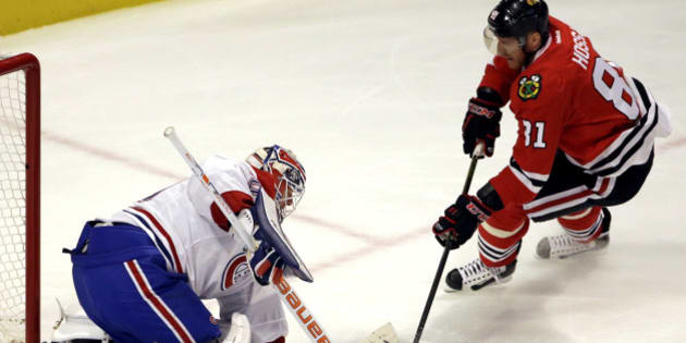 Montreal Canadiens goalie Ben Scrivens, left, saves a shot by Chicago Blackhawks right wing Marian Hossa during the first period of an NHL hockey game Sunday, Jan. 17, 2016, in Chicago. (AP Photo/Nam Y. Huh)