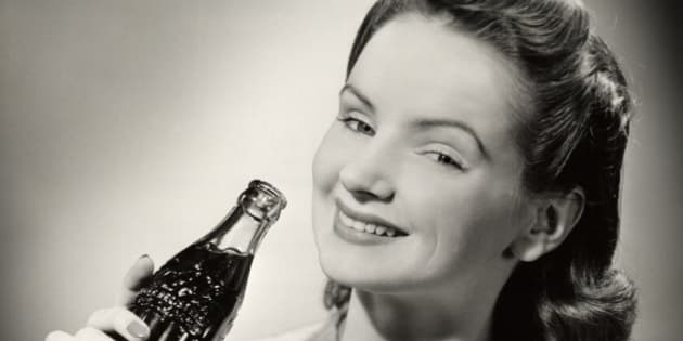 UNITED STATES - CIRCA 1950s:  Teenage girl with bottle of Coca-Cola.