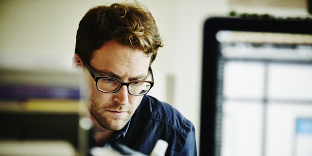 Businessman working on project on laptop in startup office