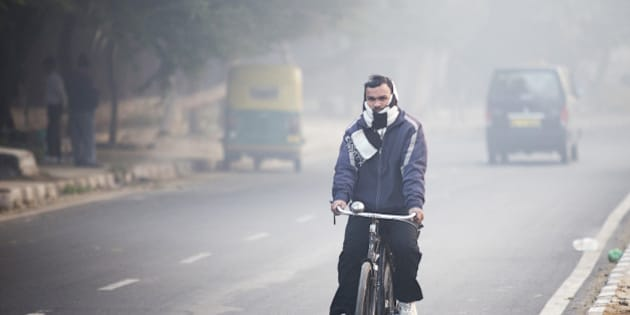 A cyclist travels along a road shrouded in smog in New Delhi, India, on Monday, Jan. 11, 2016. A 2-judge Delhi High Court panel headed by Chief Justice G. Rohini allowed the odd-even traffic restrictions to continue. The measure by Delhi Chief Minister Arvind Kejriwal is the most concerted effort by the government yet to reduce the number of exhaust-belching automobiles in the world's most polluted metropolitan area as discontent among the city's 16.8 million residents grows. Photographer: Prashanth Vishwanathan/Bloomberg via Getty Images