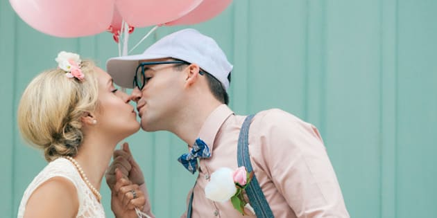 Wedding, romantic couple kissing, in retro, vintage style, with balloons.