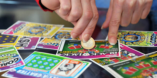 A player scratches a game card of the Française des Jeux (FDJ), the operator of France's national lottery, on May 28, 2013 in Nantes.   AFP PHOTO / FRANK PERRY        (Photo credit should read FRANK PERRY/AFP/Getty Images)