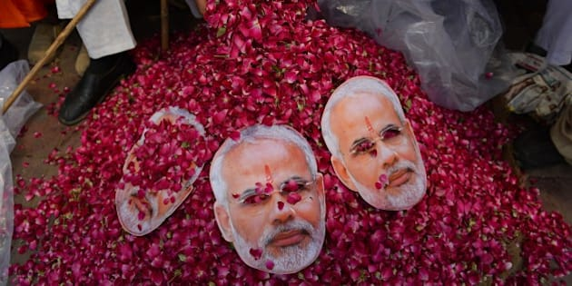 An Indian supporter of the Chief Minister of the western Indian state of Gujarat and Bharatiya Janata Party (BJP) prime-ministerial candidate Narendra Modi collects flowers ahead of his arrival in New Delhi on May 17, 2014. Hundreds of flag-waving supporters mobbed Indian prime minister-elect Narendra Modi as he arrived in New Delhi, smiling and flashing victory signs after his party's crushing poll victory. AFP PHOTO / Chandan KHANNA        (Photo credit should read Chandan Khanna/AFP/Getty Images)