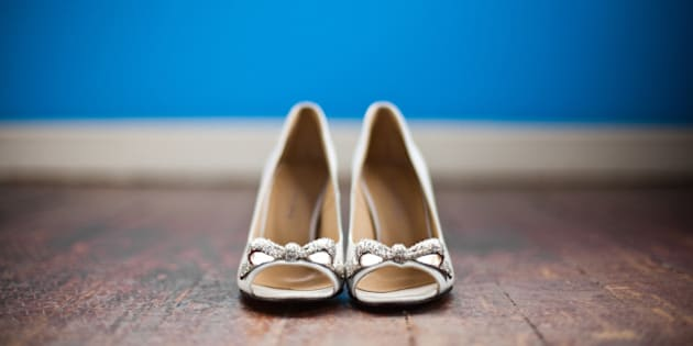 Cute shoes with bow tie on wood floor with blue background.
