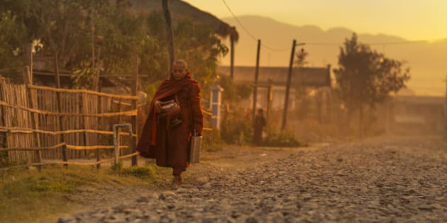 Buddhist monk goes from door to door to collect food and provide prayers in return.