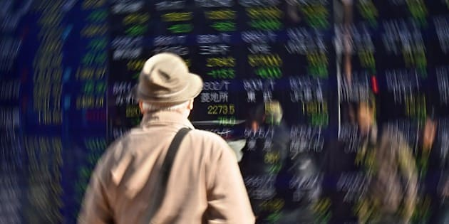 A pedestrian looks at a screen showing movements for the Tokyo Stock Exchange in Tokyo on January 14, 2016. The benchmark Nikkei 225 index at the Tokyo Stock Exchange tumbled 2.68 percent, or 474.68 points, to 17,240.95 at the close, after losing nearly four percent at one stage. AFP PHOTO / KAZUHIRO NOGI / AFP / KAZUHIRO NOGI        (Photo credit should read KAZUHIRO NOGI/AFP/Getty Images)