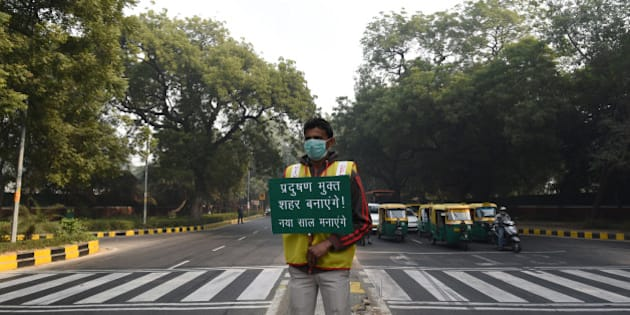 NEW DELHI, INDIA - JANUARY 4: A volunteer holds a placard for pollution free capital at APJ Kalam crossing during the Delhi's odd-even traffic arrangements on January 4, 2016 in New Delhi, India. Contrary to apprehensions, Delhi's odd-even vehicle scheme aimed at battling pollution did not lead to the feared problems on Monday, the first full working day of the New Year. The 15-day odd-even scheme started on January 1 and aims to put odd numbered vehicles on the roads on odd dates and even numbered vehicles on even dates. (Photo by Vipin Kumar/Hindustan Times via Getty Images)