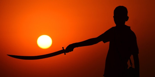 RAJASTHAN, INDIA - 2015/11/19: A child standing with a sword in hand during the sunset at the annual cattle fair in Pushkar, western Rajasthan state. Pushkar is a popular Hindu pilgrimage spot that is also frequented by foreign tourists who come to the town for its annual cattle fair. (Photo by Shaukat Ahmed/Pacific Press/LightRocket via Getty Images)