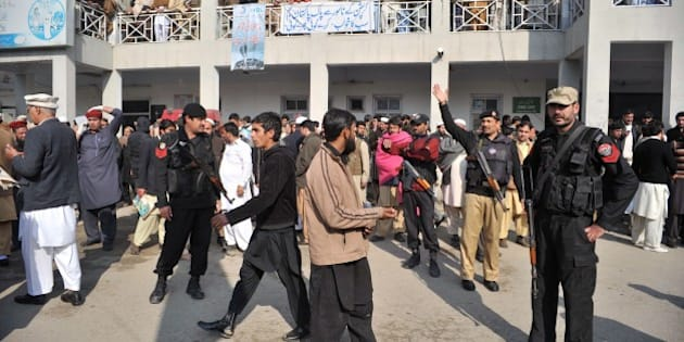 Pakistani police and onlookers gather in front of a hospital following an attack by gunmen at Bacha Khan university in Charsadda, about 50 kilometres from Peshawar, on January 20, 2016. At least 21 people died in an armed assault on a university in Pakistan on January 20, where witnesses reported two large explosions as security forces moved in under dense fog to halt the bloodshed. AFP PHOTO /Hasham AHMED / AFP / HASHAM AHMED        (Photo credit should read HASHAM AHMED/AFP/Getty Images)