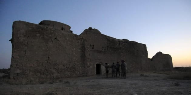 In this Aug. 21, 2009, photo released by the U.S. Army, visitors assigned to the Logistic Civil Augmentive Program from Forward Operating Base Speicher, near Tikrit, Iraq, stand at the entrance to the ruins of St. Elijah's Monastery after completing a tour there, at Forward Operating Base Marez in Mosul, Iraq. The 1,400-year-old monastery has been reduced to a field of rubble, yet another victim of the Islamic State's relentless destruction. (MC1 (SCW) Carmichael Yepez/U.S. Army via AP)
