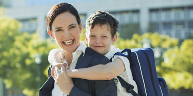 Businesswoman and son hugging in urban park