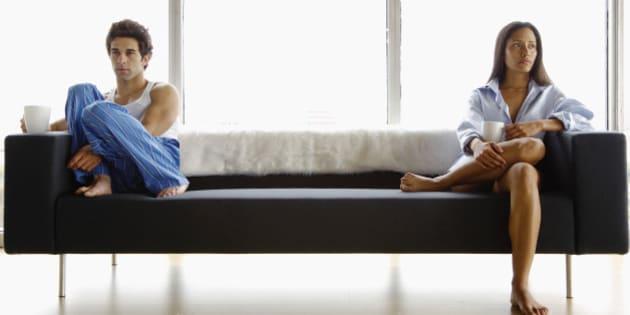 Disinterested couple sitting on sofa
