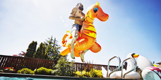 Man jumping into outdoor pool with inflatable pool toy on summer afternoon