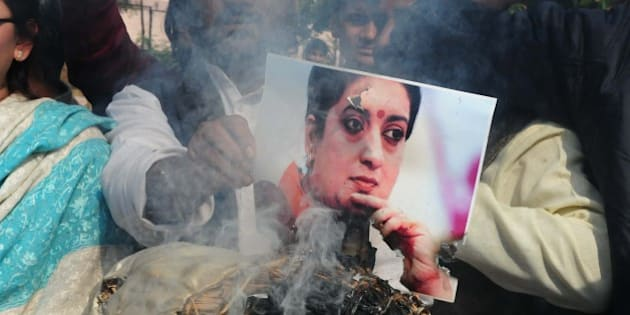 BHOPAL, INDIA - JANUARY 20: Congress workers burning an effigy of union HRD Minister Smriti Irani while protesting over the death of Rohith Vemula, a doctorate student at the Hyderabad Central University who was found hanging in the campus hostel room, on January 20, 2016 in Bhopal, India. 26-year-old Vemula committed suicide on Sunday night. He was among the five research scholars who were suspended by the Hyderabad Central University in August last year over an alleged assault case. They were also kept out of the hostel. The five were allegedly suspended after BJP leader Bandaru Dattatreya wrote a letter to HRD Minister Smriti Irani, describing the university as a 'den of casteist, extremist and anti-national politics'. (Photo by Arijit Sen/Hindustan Times via Getty Images)