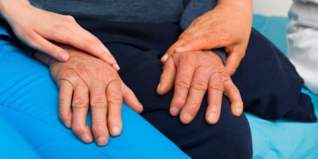 Caring hands of a nurse and doctor for elderly patient with Parkinson's disease.