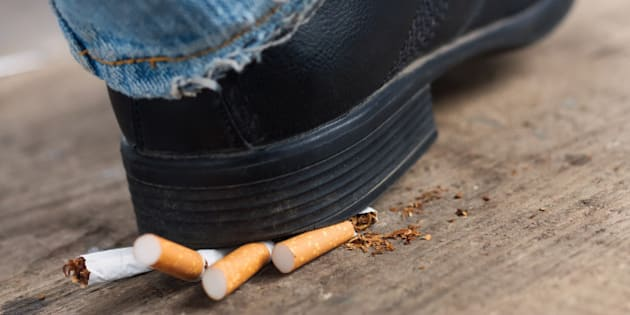 Man quit smoking and crush cigarettes foot