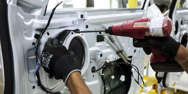 An employee uses a drill to fit a speaker to the door of a Mahindra & Mahindra Ltd. XUV 500 sport-utility vehicle (SUV) on the production line at the company's facility in Chakan, Maharashtra, India, on Wednesday, Sept. 12, 2014. Mahindra, Indias largest maker of tractors and sport-utility vehicles, is in advanced talks to buy PSA Peugeot Citroens scooter business, according to three people familiar with the matter. Photographer: Udit Kulshrestha/Bloomberg via Getty Images