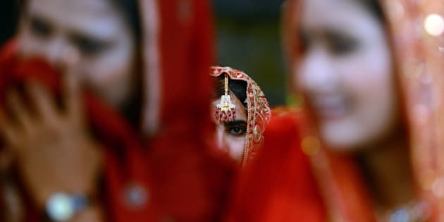 Pakistani brides attend a mass marriage ceremony in Karachi late March 26, 2013.  Some 110 couples participated in the mass wedding ceremony organised by a local charity welfare trust Al Ghousia. AFP PHOTO / ASIF HASSAN        (Photo credit should read ASIF HASSAN/AFP/Getty Images)