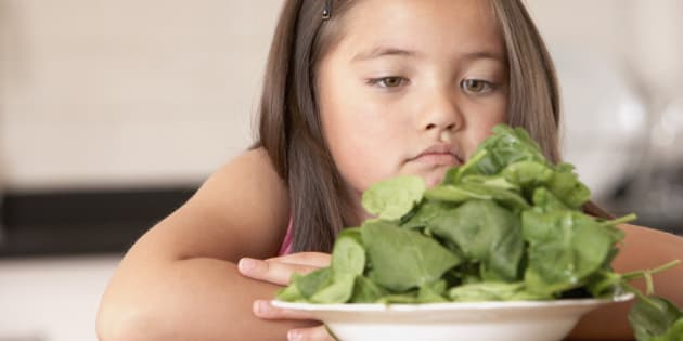 Young girl in kitchen with a bowl of spinach looking unhappy