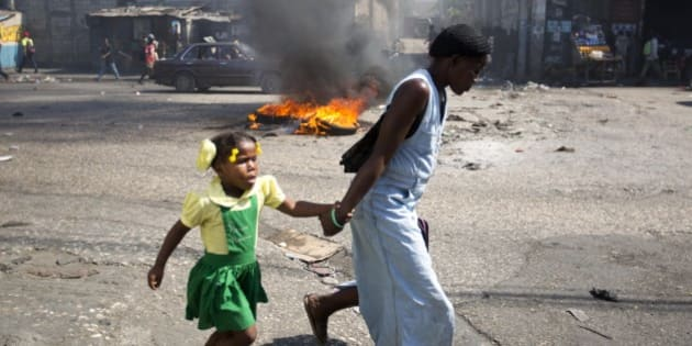A woman and a child walk past a burning barricade during a protest against President Michel Martelly's government to demand the cancellation of the Jan. 24, elections, in Port-au-Prince, Haiti, Monday, Jan. 18, 2016. Disputed election results have brought paralyzing street protests and many broad accusations of electoral fraud from civil society and opposition groups. (AP Photo/Dieu Nalio Chery)