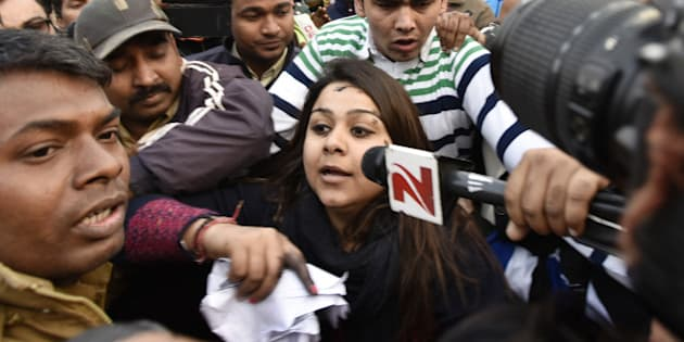 NEW DELHI, INDIA - JANUARY 17: A woman (C) who threw ink on Chief Minister Arvind Kejriwal (Not in Picture) during the thanksgiving event of odd-even scheme at Chhatrasal Stadium on January 17, 2016 in New Delhi, India. The woman identified as Bhavna, claimed to be a member of Aam Aadmi Sena, accused Kejriwal of doing CNG scam. (Photo by Sanjeev Verma/Hindiustan Times via Getty Images)