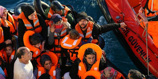 IZMIR, TURKEY -  JANUARY 20: Turkish Coast Guard members intervene in a boat carrying refugees, who were trying to go to Greek Islands, after being caught by the TCSG 'Guven' Ship belonging to the Turkish Coast Guard near the coast of Cesme district of Izmir, Turkey on January 20, 2016. There are a striking number of children among the refugees forced to journey on despite bad weather conditions in hope of reaching Europe. (Photo by Emin Menguarslan/Anadolu Agency/Getty Images)