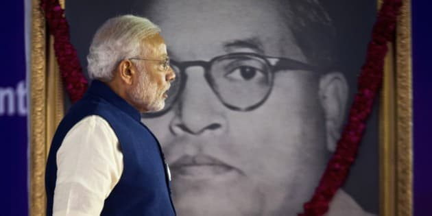Indian Prime Minister Narendra Modi walks by a photograph of Bhim Rao Ambedkar  during the unveiling ceremony of the foundation stone for an international center dedicated to Ambedkar, in New Delhi, India, Monday, April 20, 2015. Ambedkar, an untouchable, or Dalit, and a prominent Indian freedom fighter, was the chief architect of the Indian Constitution, which outlawed discrimination based on caste.(AP Photo/Saurabh Das)