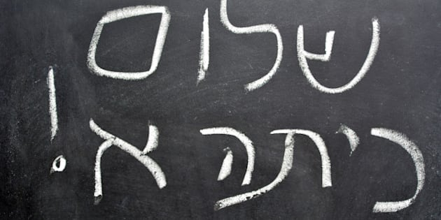 Hello First Grade greetings in Hebrew (Shalom Kita Alef) on a chalkboard in Israeli primary school at the beginning of the school year.Concept photo of early age education,learning ,studying, teaching