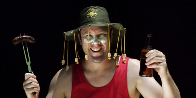 An Aussie man in a cork hat smiles at the camera holding up a sausage on a fork in one hand and a beer in the other