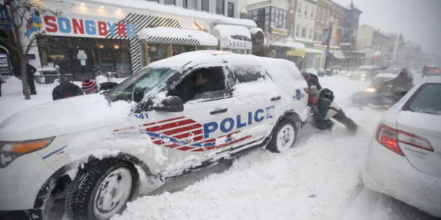 People pitch in to get a DC Metro police car moving again on 18th Street NW, Saturday, Jan. 23, 2016 in Washington. A blizzard with hurricane-force winds brought much of the East Coast to a standstill Saturday, dumping as much as 3 feet of snow, stranding tens of thousands of travelers and shutting down the nation's capital and its largest city. (AP Photo/Alex Brandon)