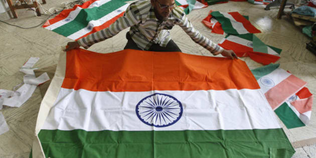 An Indian man prepares to fold an Indian flag being made at a factory ahead of Independence Day in Ahmadabad, India, Tuesday, Aug. 11, 2015. India celebrates its Independence Day on August 15. (AP Photo/Ajit Solanki)