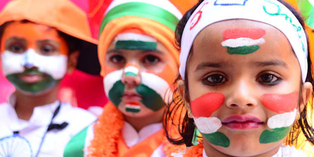 RAJASTHAN, INDIA - 2016/01/25: Indian first step school children paint the tricolor of Indian flag on their face and  raise the National Flag on the eve of republic day celebrations in Rajasthan, India. (Photo by Shaukat Ahmed/Pacific Press/LightRocket via Getty Images)