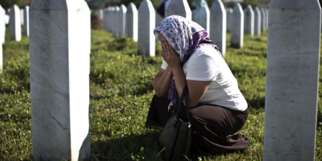 A woman cries as she visits the grave of a family member at the Potocari memorial complex near Srebrenica, 150 kilometers (94 miles) northeast of Sarajevo, Bosnia and Herzegovina, Saturday, July 11, 2015. Twenty years ago, on July 11, 1995, Serb troops overran the eastern Bosnian Muslim enclave of Srebrenica and executed some 8,000 Muslim men and boys, which International courts have labeled as an act of genocide, and newly identified victims of the genocide are still being re-interred at Srebrenica. (AP Photo/Marko Drobnjakovic)