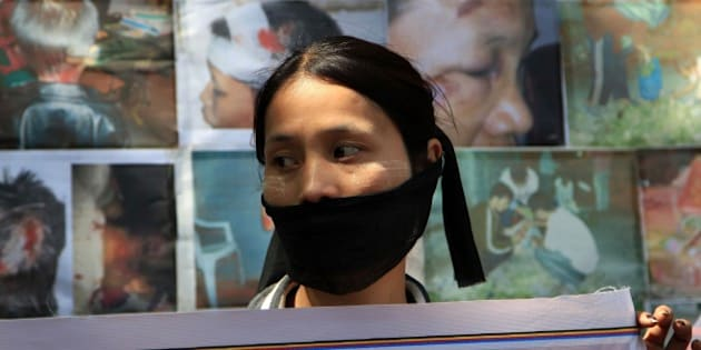 A Myanmarese refugee woman covers her mouth with a black cloth and participates in a protest on International Women's Day in New Delhi, India Saturday, March 8, 2014. Myanmarese in Delhi alleged their government used forms of violence against women as weapons of war and demanded an end to it. They also urged India for protection from sexual violence, healthcare and education for their children in India. (AP Photo/Tsering Topgyal)