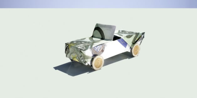 Origami car folded with 100 euro notes and coins