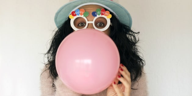 Young woman with birthday hat and birthday glasses, blowing pink balloon. White background.