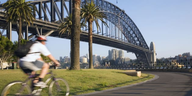 Australia, New South Wales, Sydney. An early morning cyclist rounds Daves Point Reserve at the foot of the Harbour Bridge on Sydney Cove