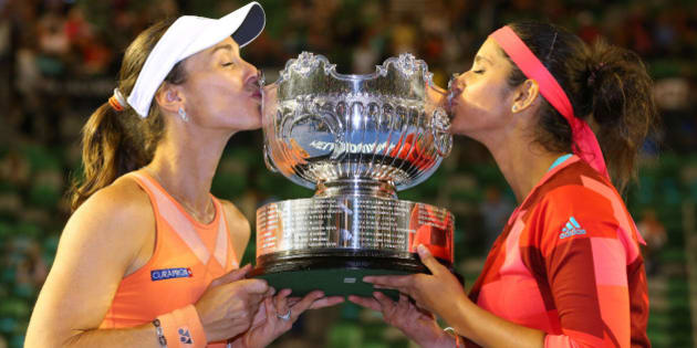 MELBOURNE, AUSTRALIA - JANUARY 29:  Martina Hingis of Switzerland and Sania Mirza of India pose with the championship trophy after winning their women's doubles final match against Andrea Hlavackova and Lucie Hradecka of the Czeck Republic during day 12 of the 2016 Australian Open at Melbourne Park on January 29, 2016 in Melbourne, Australia.  (Photo by Scott Barbour/Getty Images)