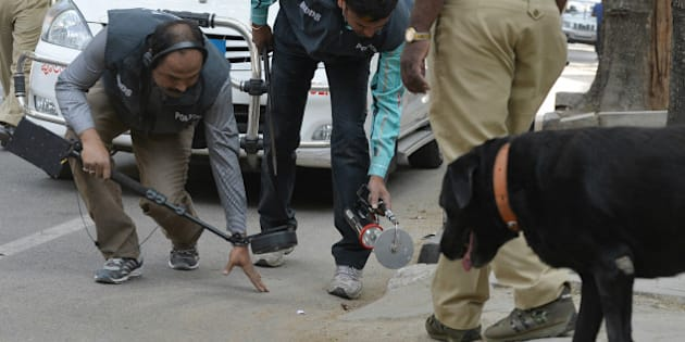 Indian bomb-disposal personnel and police sniffer dogs search an area where an unidentified package was found at the roadside in Bangalore on January 15, 2016. Ppolice later confirmed the incident was a false alarm. AFP PHOTO / Manjunath KIRAN / AFP / MANJUNATH KIRAN        (Photo credit should read MANJUNATH KIRAN/AFP/Getty Images)
