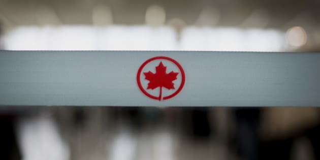 The Air Canada logo is seen on a rope at a check-in counter at Toronto Pearson International Airport in Toronto, Ontario, Canada, on Wednesday, July 3, 2013. Air Canada predicted further pressure on fares this year after its first-quarter yield dropped as competitors added seating and offered lower prices on some routes in North and South America. Photographer: Brent Lewin/Bloomberg via Getty Images