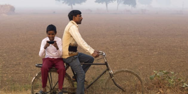 India, Uttar Pradesh, Agra, Indian man riding bike with village boy loking at photos on a smartphone.