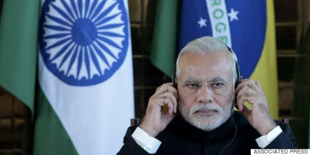 India's Prime Minister Narendra Modi adjusts his headset during a signing ceremony with Brazil's President Dilma Rousseff at Palacio da Alvorada, or Palace of the Dawn, in Brasilia, Brazil, Wednesday, July 16, 2014. (AP Photo/Eraldo Peres)