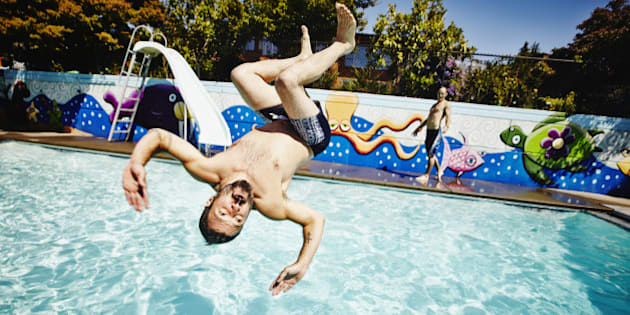 Man doing backflip into outdoor swimming pool on summer afternoon with friend watching in background