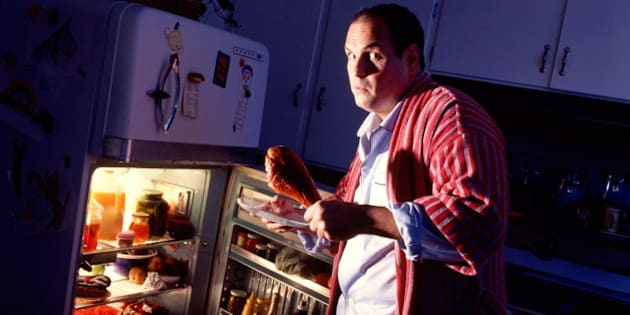 Man looking shocked, taking food out of refrigerator at night