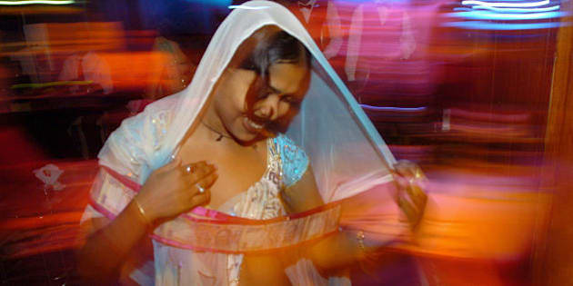 BOMBAY, INDIA:  An Indian bar dancer dances with a garland of currency notes offered by a customer during a  performance at a suburban bar cum resturant  in Bombay, 06 May 2005. The western state of Maharashtra has decided to shut down 'dance bars' or drinking houses featuring scantily-clad dancers in the capital Bombay, which had escaped a state-wide crackdown last month. Nearly 1,500 dance bars operate in Maharashtra employing more than 100,000 women, most of whom style and ape their performances on elaborate Bollywood song-and-dance musical numbers for customers looking for food, liquor and entertainment whilst police claim that many of the bars double as pick-up joints.  AFP PHOTO/ Indranil MUKHERJEE.  (Photo credit should read INDRANIL MUKHERJEE/AFP/Getty Images)