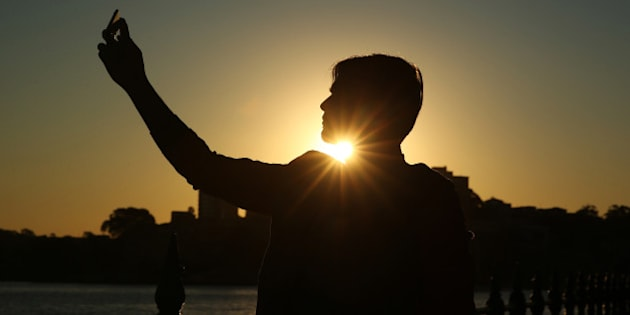 A tourist from Pakistan poses for a 'selfie' photograph as the sun sets in Sydney, Australia, on Tuesday, July 21, 2015. Tired hotels, outdated attractions like Sydney's Darling Harbor and mediocre customer service mean Australia's tourism industry isn't making the most of a booming Chinese travel market at a time when it needs all the economic help it can get. Photographer: Brendon Thorne/Bloomberg via Getty Images