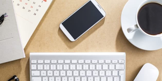 Wireless keyboard, mouse and cell phone on table