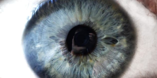 Close up of open human eye with photographer reflection.