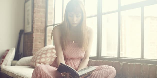 Young Woman reading book in apartment
