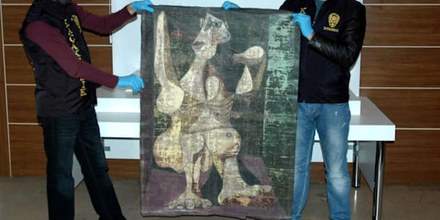 Turkish police from the Istanbul Police Department Anti-Smuggling and Organized Crime Unit, hold-up an original painting by Spanish artist Pablo Picasso, 'Woman Dressing Her Hair', on January 30, 2016, in Istanbul. 